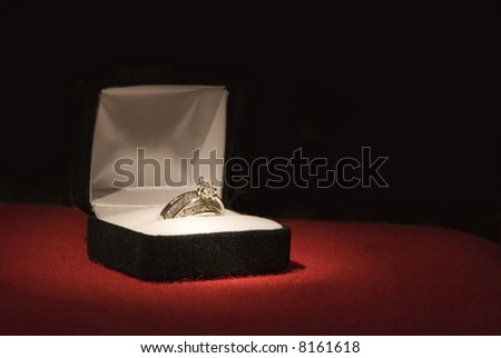 A beautiful 2 carat wedding ring on red felt with black background and shallow DOF - stock photo