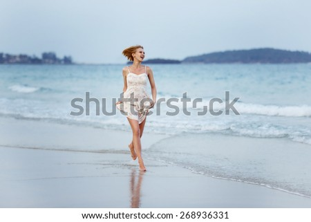 A beautiful carefree girl is running along a sea shore at blue waves background. - stock photo