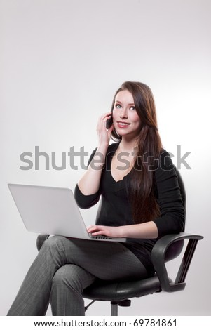 A beautiful caucasian businesswoman talking on the phone while working on her laptop