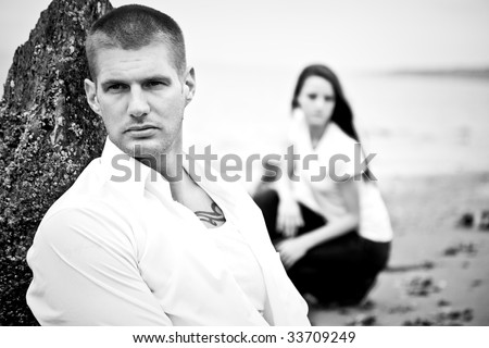 A beautiful caucasian couple in love sitting on the beach (in black and white)