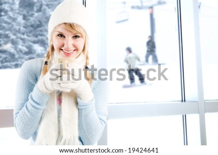 A beautiful caucasian girl drinking hot coffee at a ski resort - stock photo