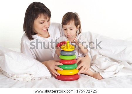 A beautiful Caucasian girl with her mama play in the bed