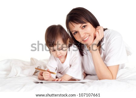 A beautiful Caucasian mummy with her daughter lying on the bed with a pencil