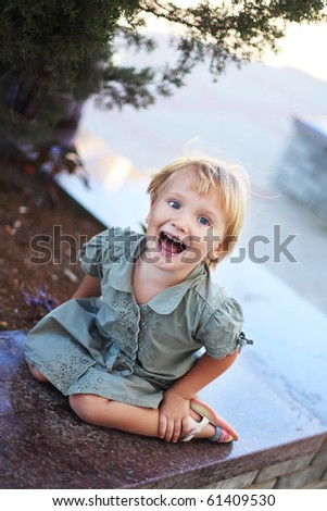 A beautiful caucasian white blond baby girl in green clothes with happy expression in her face screaming