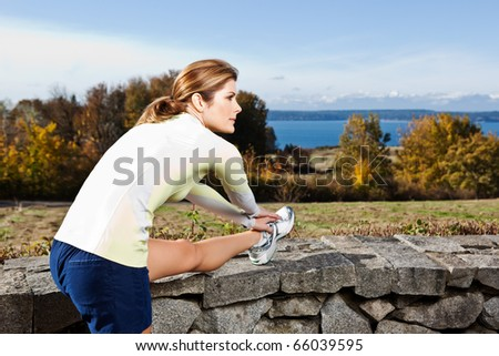A beautiful caucasian woman doing exercise outdoor in a park - stock photo