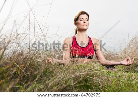 A beautiful caucasian woman doing yoga meditation outdoor in a park - stock photo