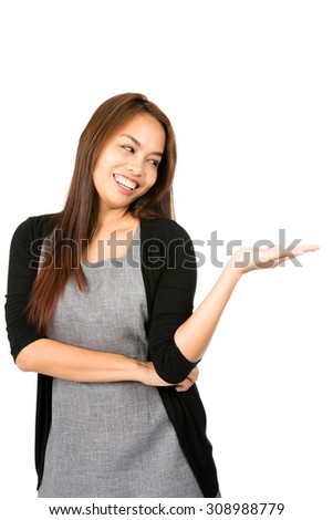 A beautiful, cheerful Asian woman in black sweater with flat open palm showing imaginary inserted product looking down at hand to the side. Thai national of Chinese origin. Vertical - stock photo