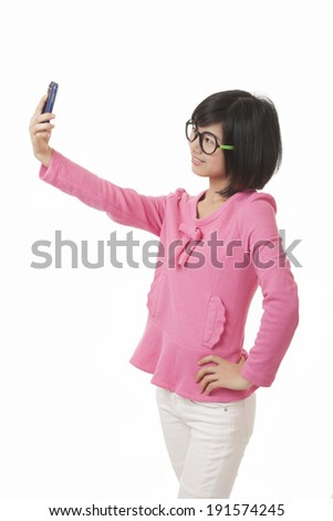 A beautiful Chinese woman using a cell phone to take a selfie on a white background - stock photo