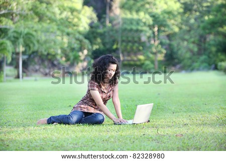 A beautiful college student working on her laptop on campus