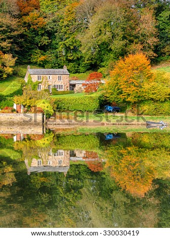 A beautiful cottage surrounded by Autumn colour and reflected in a lake - stock photo