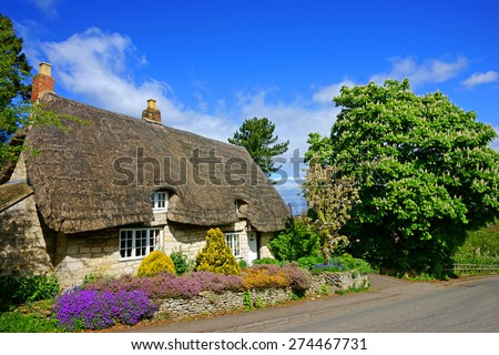 A Beautiful Country Cottage With Thatched Roof In Spring Time The Cotswolds Gloucestershire