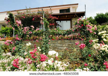 a beautiful country house surrounded by a garden full of flowers - stock photo
