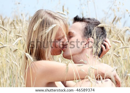 A beautiful couple sitting an kissing in wheat field - stock photo