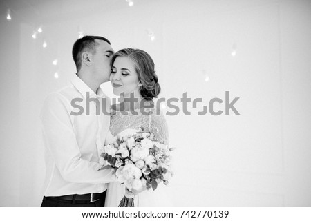 A beautiful couple. The bridegroom is kissing the bride. A beautiful and stylish wedding bouquet in hands.black and white photo