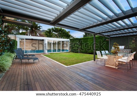 a beautiful courtyard with a lawn and swimming pool . barbecue area