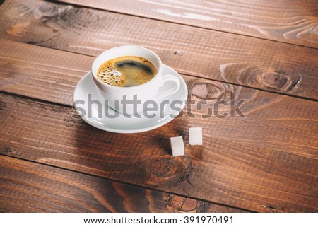 a beautiful Cup of coffee with two lumps of sugar cubes on old wooden background - stock photo
