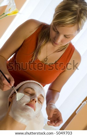 A beautiful dark haired woman receives a face mask treatment from a young blond beautician - stock photo