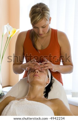A beautiful dark haired woman receives a facial treatment from a young blond beautician - stock photo