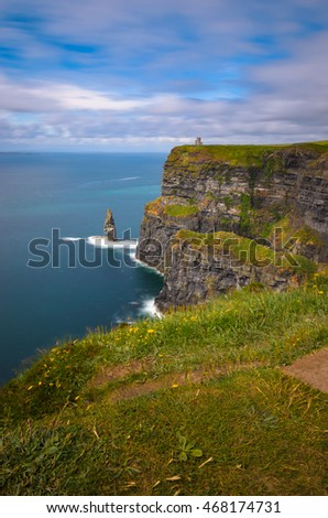 A beautiful day at the Cliffs of Moher looking out to O'Brien's Tower with smooth blue water below in County Clare, Ireland