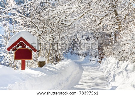 A beautiful day in winter wonderland. Snowcapped trees over snowy country road. - stock photo