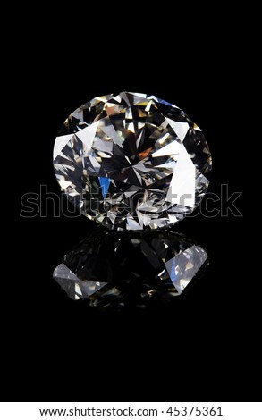 A beautiful diamond on a dark reflective surface - stock photo