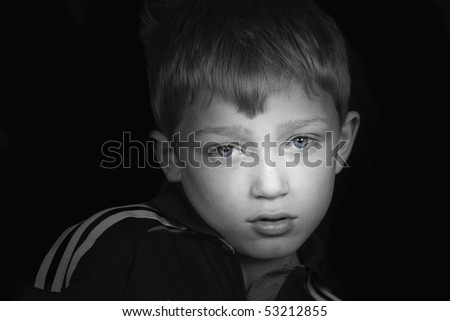 a beautiful dramatic portrait of a young blonde boy in black and white