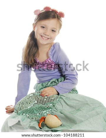 A beautiful elementary girl happily sitting with her pet hermit crab.  On a white background. - stock photo