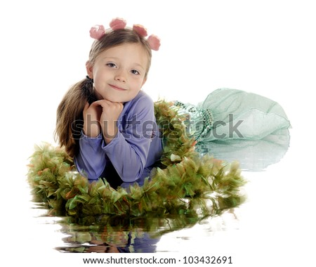 """A beautiful elementary girl posed as a mermaid on """"sea weed"""" and with a watery reflection.  On a white background. - stock photo"""
