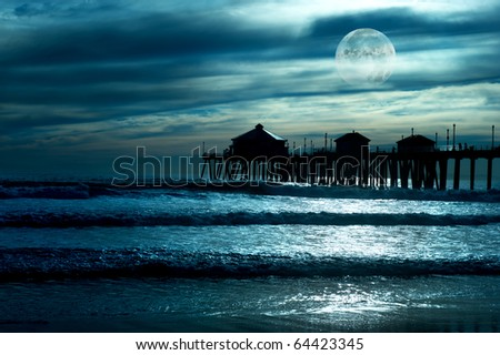 A beautiful evening along the beach shows a pier during a low moon with reflections in the water, and a moody sky. - stock photo