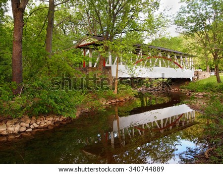 A beautiful example of a traditional wooden covered bridge, crossing Dunning's Creek and reflecting on the water, in Bedford County, Pennsylvania.  - stock photo
