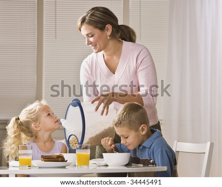 A beautiful family eating breakfast together. The mother is smiling and is pouring cereal for the daughter.  Horizontally framed shot. - stock photo