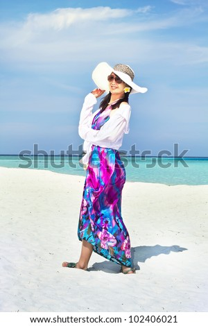 A beautiful fashion asian girl playing water in Maldive beach near the ocean in the hot summer