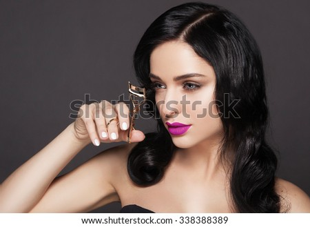 A beautiful fashion girl with bright lips holding an eyelash curler in her hand as a makeup accessory.
