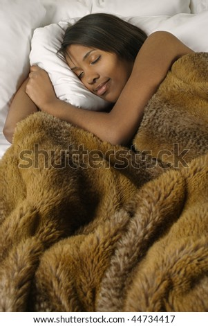 A beautiful female sleeping comfortably under warm blankets. - stock photo