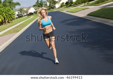 A beautiful fit and healthy blond woman road running down a suburban street in summer sunshine