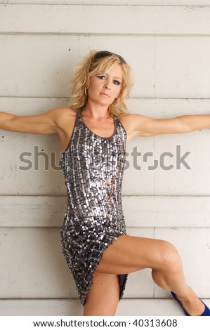 A beautiful fit muscular woman is standing against wall with her arms outstretched and her leg bent, looking at viewer. - stock photo