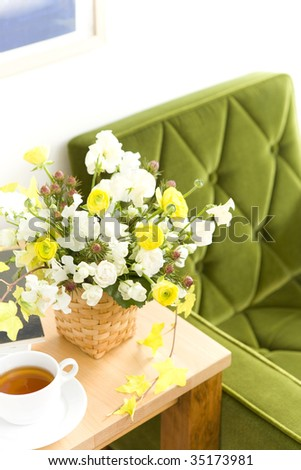 A beautiful flower arrangement on the table with a cup of tea - stock photo