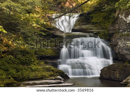 A beautiful 20 foot waterfall in Enfield Glen , New York. Early evening sunlight highlights the leaves along the stream and adds to the beauty of the scene. - stock photo