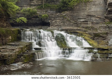 A  beautiful 20 foot waterfall in Enfield Glen which is in Robert Treman state park, New York. Green moss, lichens and ferns along the gorge walls add to the beauty of the scene. - stock photo