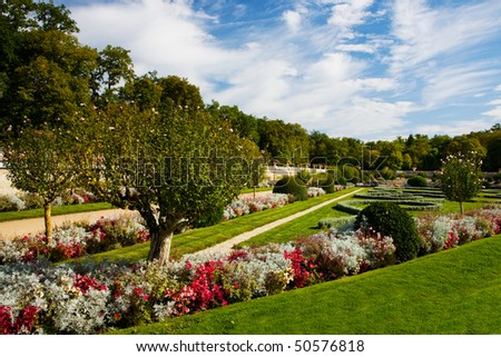 A beautiful formal garden in France, with flowers, plants and sculpted hedges, on a sunny day. - stock photo
