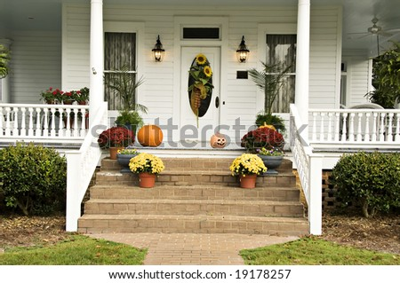 A beautiful front porch decorated for fall with sunflowers, mums, pumpkins, pansies, and a jack-o-latern - stock photo