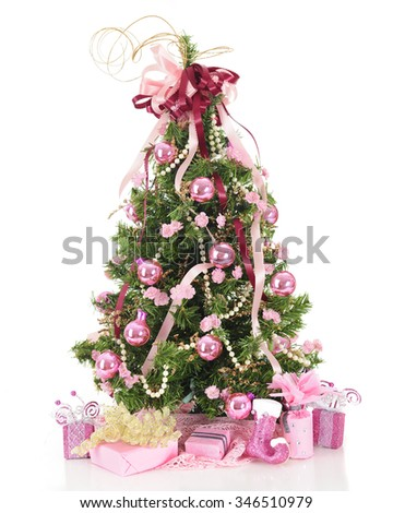 A beautiful, full Christmas tree decorated in pearls and pink  flowers, ribbons and shiny bulbs.  A lacy pink skirt and pretty pink-decorated gifts  surround the base.  On a white background. - stock photo