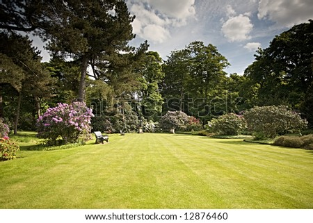 A beautiful garden with ornamental flowering shrubs and a striped lawn - stock photo