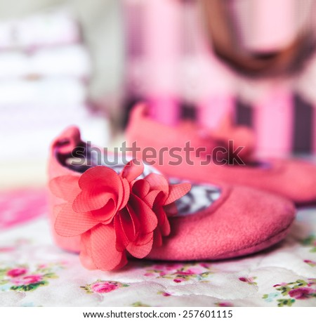 A beautiful gift for a newborn, diapers, pacifiers, peach shoes and gift wrap - stock photo