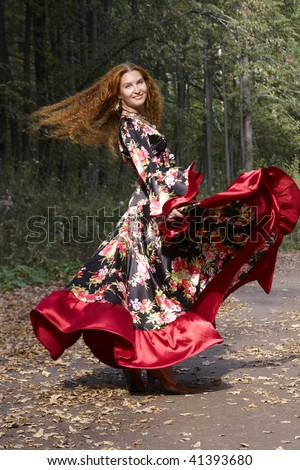A beautiful ginger-haired girl in gipsy suit in dance whirlwind