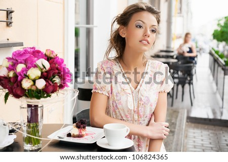 A beautiful girl are sitting in a cafe and drinking tea. Outdoors - stock photo