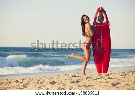 A beautiful girl at the beach holding her surfboard - stock photo