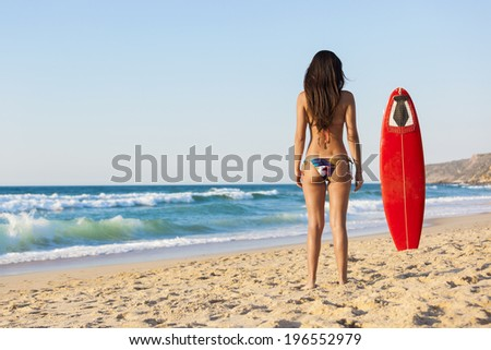 A beautiful girl at the beach posing with her surfboard - stock photo