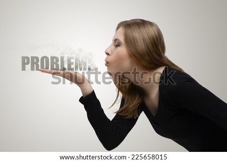 a beautiful girl blowing off the problems - stock photo
