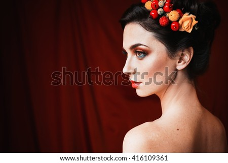 a beautiful girl, brunette woman with brown eyes with bright makeup, make-up with berries and flowers in hair, red lips, unusual appearance, a woman with tanned skin on red dark background, profile - stock photo
